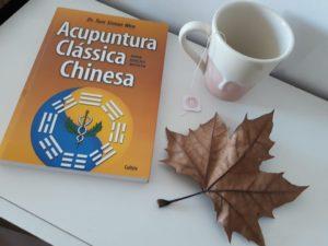 Foto de livro de acupuntura, xícara e folha seca numa mesa
