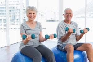 Casal de idosos sentado numa bola de pilates com halteres nas mãos