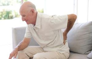 Homem idoso com a mão na coluna lombar