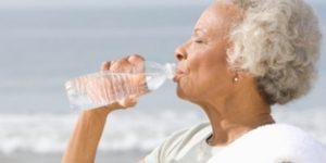 Foto de idosa numa praia tomando água mineral