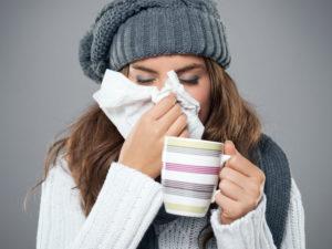 Foto de mulher com resfriado e xícara nas mãos