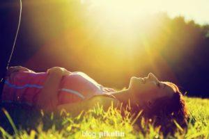 Mulher deitada na grama em dia ensolarado