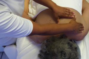 mãos fazendo drenagem linfatica nas costas de uma mulher