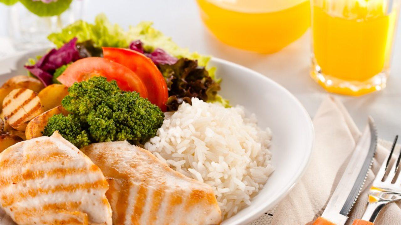 prato contendo arroz, frango, brócolis e tomate